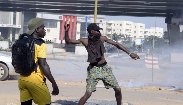 Un manifestant jette une pierre lors d'une manifestation de membres de l'opposition guinéenne, dans une rue menant à l'ambassade de Guinée à Dakar, le 21 octobre 2020. - Alors que les tensions sont déjà vives, le principal chef de l'opposition guinéenne Cellou Dalein Diallo a déclaré le 19 octobre sa victoire à l'élection - avant l'annonce des résultats officiels, qui sont attendus cette semaine. Les partisans de l'opposition sont profondément méfiants quant à l'équité du scrutin, bien que le gouvernement insiste sur le fait qu'il était juste. (Photo par Seyllou / AFP)