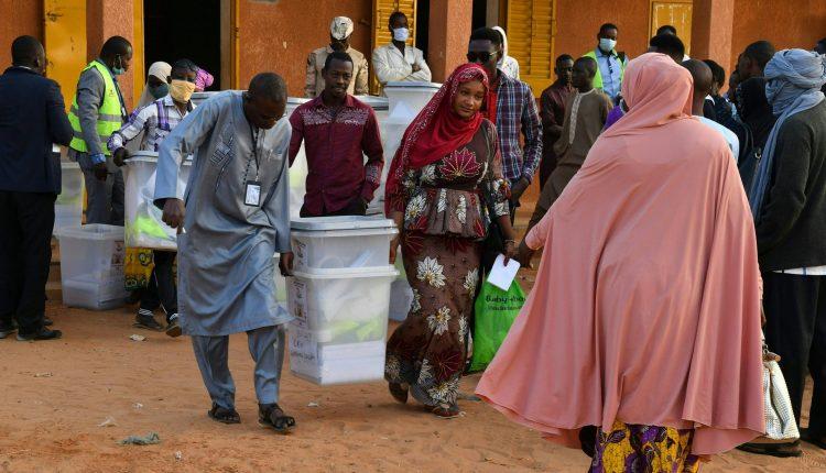 Des responsables de la commission électorale transportent des urnes devant un bureau de vote à Niamey le 27 décembre 2020 lors des élections présidentielles et législatives au Niger. - Les électeurs de l'État sahélien du Niger se rendent aux urnes le 27 décembre 2020 pour une élection qui pourrait sceller la toute première passation de pouvoir pacifique du pays entre les présidents élus, malgré une insurrection djihadiste sanglante. (Photo par Souleymane AG ANARA / AFP)